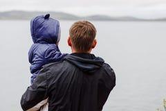 Un homme dans une veste avec un enfant dans des ses bras se tient sur le lac, de nouveau à l'appareil-photo, au printemps photo libre de droits