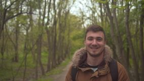 Un homme dans une veste chaude de broun marche par les bois L'homme entre dans l'avant, la caméra suit le sien clips vidéos