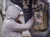 Un homme dans une veste légère dans le capot appelle une vieille cabine téléphonique photos stock