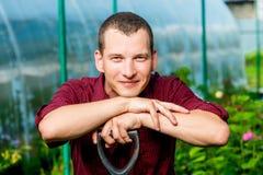 Un homme de 30 ans reposant ses coudes sur une pelle Photo libre de droits