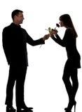 Un homme de couples offrant la fleur et la femme roses Photo stock