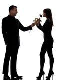 Un homme de couples offrant sentir rose de fleur et de femme Photographie stock libre de droits
