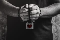 Un homme de deux mains enchaînées avec la vieille chaîne rouillée et le coeur rouge SH Photo libre de droits