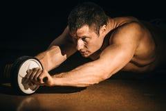 Un homme de forme physique secoue une presse avec une roue photo stock