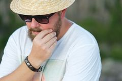Un homme de hippie dans les lunettes de soleil et un chapeau de paille avec une barbe Photo stock