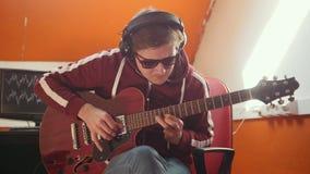 Un homme de musicien dans des écouteurs fonctionnant dans le studio Jeu de la guitare clips vidéos