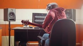 Un homme de musicien s'asseyant par l'ordinateur dans le studio et enregistrant une chanson Prenant des écouteurs et le mettre su banque de vidéos