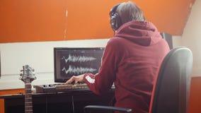 Un homme de musicien travaillant dans le studio sain Mise sur des écouteurs et débuts jouant le Midi-clavier banque de vidéos