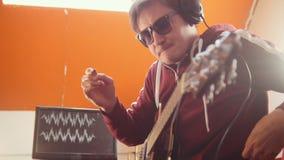 Un homme de musicien travaillant dans le studio sain Mise sur des écouteurs et jeu de la guitare banque de vidéos