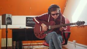 Un homme de musicien travaillant dans le studio sain Mise sur des écouteurs clips vidéos