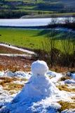 Un homme de neige fondant sur le dessus d'une colline dans la neige, Angleterre photos stock