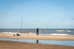 Un homme de pêcheur avec deux cannes à pêche sur la plage de la Mer du Nord images libres de droits