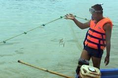 Un homme de pêcheur se tient sur son bateau avec une pile de filet de pêche Image stock