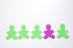 Un homme de plastique pourpre dans une rangée de vert Photos libres de droits