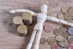 Un homme de poupée avec son argent d'économie Photo stock