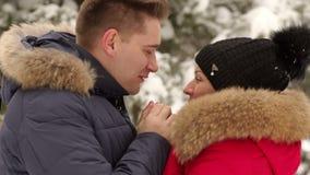 Un homme de soin chauffe ses mains du ` s d'épouse pendant l'hiver banque de vidéos