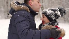 Un homme de soin enlève la neige du chapeau du ` s de fille banque de vidéos