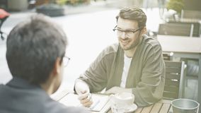 Un homme de sourire écoutant son ami dans un café dehors Photographie stock