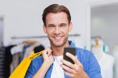 Un homme de sourire avec des paniers regardant son smartphone image libre de droits