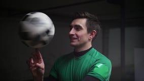 Un homme de sourire tournant la boule du football sur son doigt banque de vidéos