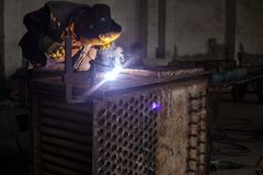 Un homme de travailleur avec le métal de soudure de masque protecteur photos stock