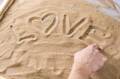 Un homme dessine par son doigt sur l'amour de mot de sable avec le symbole de Photo libre de droits