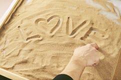 Un homme dessine par son doigt sur l'amour de mot de sable avec le symbole de du coeur Image stock