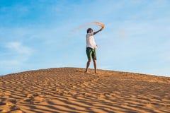 Un homme donne un coup de pied le sable dans un désert rouge Éclaboussure de concept de colère photographie stock