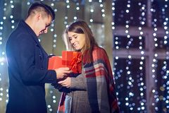 Un homme donne une boîte avec un cadeau à son amie dehors Photos stock