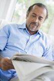 Un homme du Moyen-Orient affichant un journal à la maison Photographie stock libre de droits