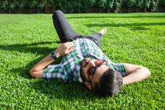 Un homme du Moyen-Orient de mode avec la barbe, coiffure de mode se repose le beau temps de jour d'herbe verte Photographie stock