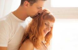 Un homme embrasse sa femme sur le sommet Image stock