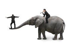 Un homme employant l'éléphant un autre d'équitation d'orateur équilibrant sur le tronc Photos libres de droits