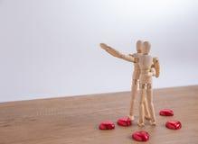 Un homme en bois de poupée le Saint Valentin sur le plancher en bois avec l'acte de l'amour et de la relation Image stock