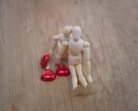 Un homme en bois de poupée le Saint Valentin sur le plancher en bois avec l'acte de l'amour et de la relation Photos libres de droits
