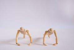 Un homme en bois de poupée s'exerce avec son ami Images stock
