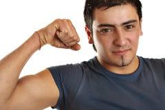 Un homme en bronze démontre son biceps images stock