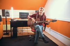Un homme en jouant la guitare dans le studio d'enregistrement sonore photo libre de droits