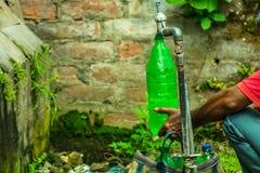 Un homme en utilisant des récipients en plastique de polycarbonate pour l'eau potable qui peut mener aux risques sanitaires série images libres de droits