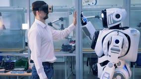 Un homme en verres de VR donne un top-là de robot banque de vidéos