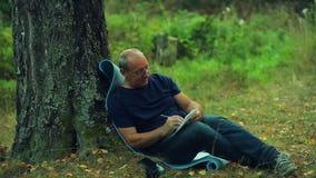 Un homme en verres s'assied sous un arbre en parc et écrit dans un carnet avec un crayon banque de vidéos