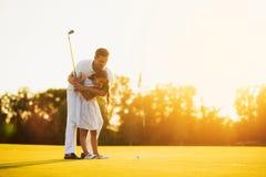 Un homme enseigne sa fille à jouer au golf Il la guide, la fille est prêt pour lui faire le premier poinçon dans le golf Images stock