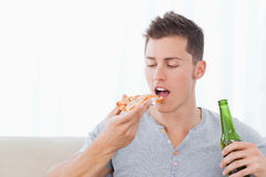 Un homme environ pour manger de la pizza comme il tient de la bière Photos libres de droits