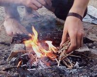Un homme essaye d'allumer un feu et jette la paille dans le feu photos libres de droits