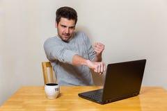 Un homme essaye d'enfermer dans une boîte son écran d'ordinateur portable tout en se reposant sur une table Photos stock