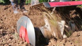 Un homme est un agriculteur dans un secteur suburbain, un potager, charrues la terre avec un cultivateur, une charrue manuelle de banque de vidéos