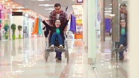 Un homme est chanceux après avoir fait des emplettes une femme handicapée dans un fauteuil roulant au mail Ils ` au sujet de avoi clips vidéos