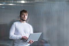Un homme est un employé de bureau se tenant sur le fond d'un mur de bureau avec un ordinateur portable dans des ses mains Un rega images stock