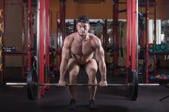 Un homme est engagé dans le bodybuilding dans le gymnase, soulève la barre et forme ses muscles images stock