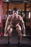 Un homme est engagé dans le bodybuilding dans le gymnase, soulève la barre et forme ses muscles photos libres de droits
